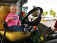 Child sits in tractor mower at Gresham's CityFest.