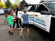 Children line up to ride in a police car at Gresham's CityFest.